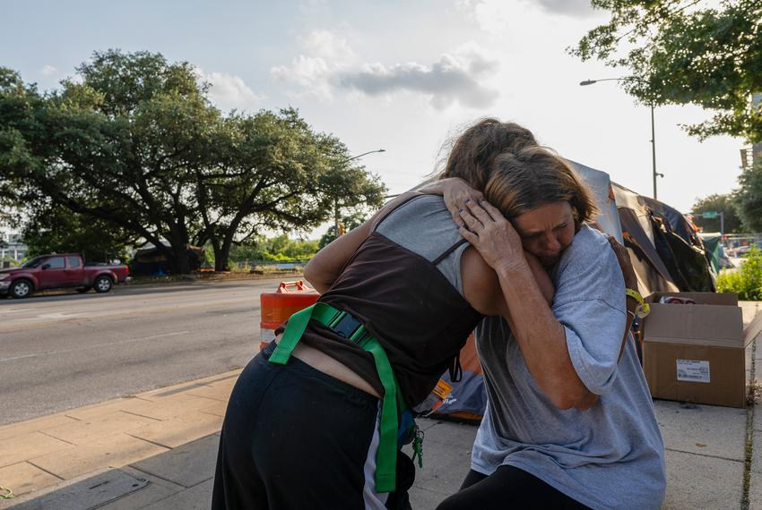 Christina Jezzizki hugs her friend Elizabeth while sitting outside her tent in front of Austin City Hall on June 21, 2021.
