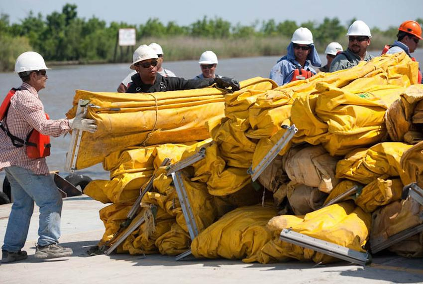 Contracted workers from U.S. Environmental Services organize boom for deployment at the Venice, La., staging area Thursday, …