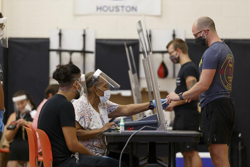 Voters check-in with poll workers behind plexiglass and cast ballots in booths spread apart in the gymnasium at the Metropol…
