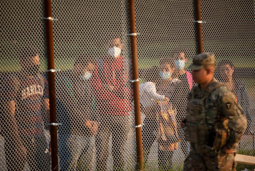 A National Guard soldier walks past a group of migrants. The group turned themselves over to Customs and Border Protection o…