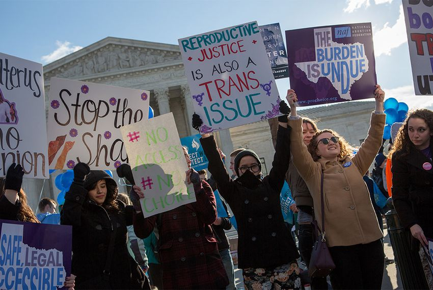 Protesters hold signs in front of the U.S. Supreme Court in Washington, D.C. as Whole Woman's Health v. Hellerstedt is argued inside.