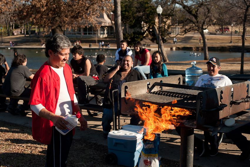 Gilberto Saucedo tends to a grill during a family barbecue in Oak Cliff's Kidd Spring Park.