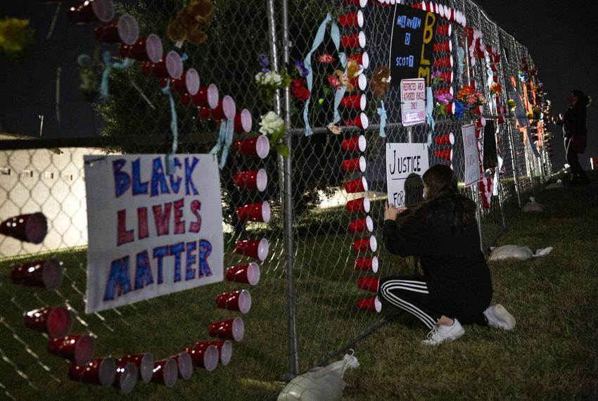 Alejandra Bernal attaches a sign to the fence surrounding the Collin County Jail nearly two weeks after Marvin Scott III die…