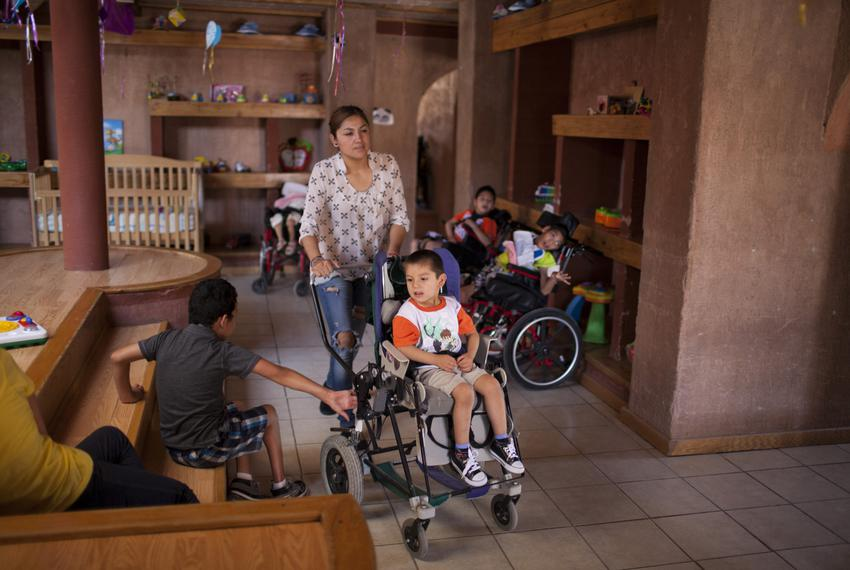 An aid worker and Aaron Sanchez, who is 3 years-old and has Gastaut syndrome, walk through the living area of the Los Ojos d…