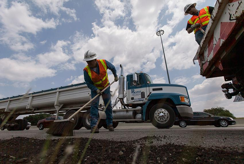 TxDOT employees Brad Shepard and Canaan Johnson finish up after putting asphalt cold mix down for edge repairs on Interstate…