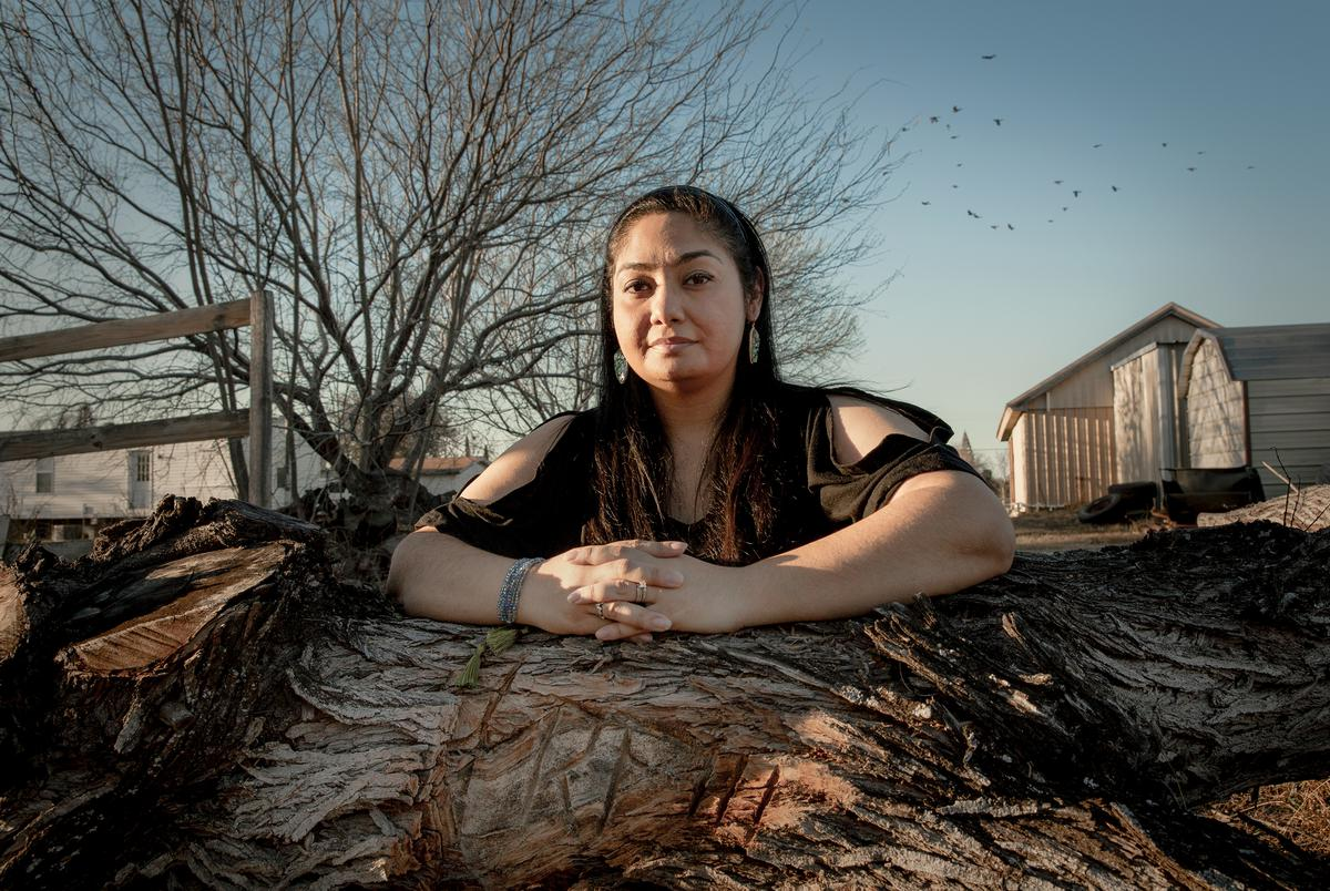 Beatrice Fuentes kneels on a mesquite tree with her husband's initials carved in the trunk. March, 5. 2021