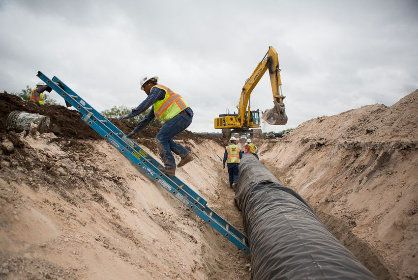 Water pipeline crew members prepare for the laying of a section of the 60-mile-long chain running near Eden, Texas, in 2012.