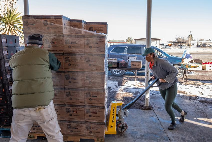 Marfa Food Pantry volunteers Gary Oliver and Alisha Waller load pallets with boxes of food for Saturday morning distribution…