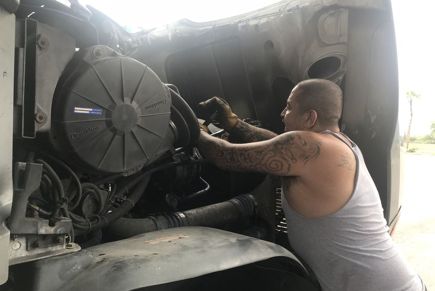 Elias Cruz, a driver for RVR Express, works on his truck during a stop at Love's Travel Stop in Edinburg. Cruz said he's been offered money by immigrants to smuggle them away from the border town.