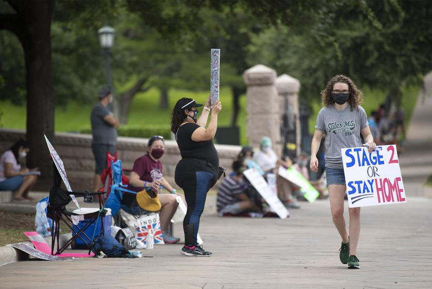Darcy Vogt Williams, who organized the protest, walks down the line of teachers outside the Capitol grounds in Austin duri...