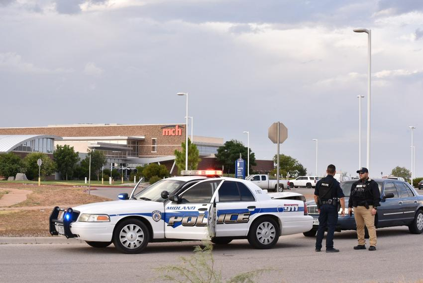 Law enforcement officers outside the Cinergy movie theater in Odessa, where a mass shooter was killed in a shootout with p...