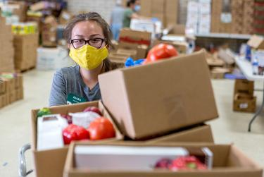 A volunteer coordinator prepares boxes of food at the Kelly Memorial Food Pantry in Central El Paso, which serves 700-1000 families a day during the COVID-19 pandemic.