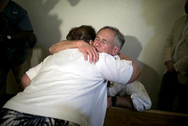 Texas GOP Gov. Greg Abbott embraces a woman after a candlelight vigil at a Catholic church, Saturday, August 3, 2019, in El Paso, Texas. Photo by Ivan Pierre Aguirre