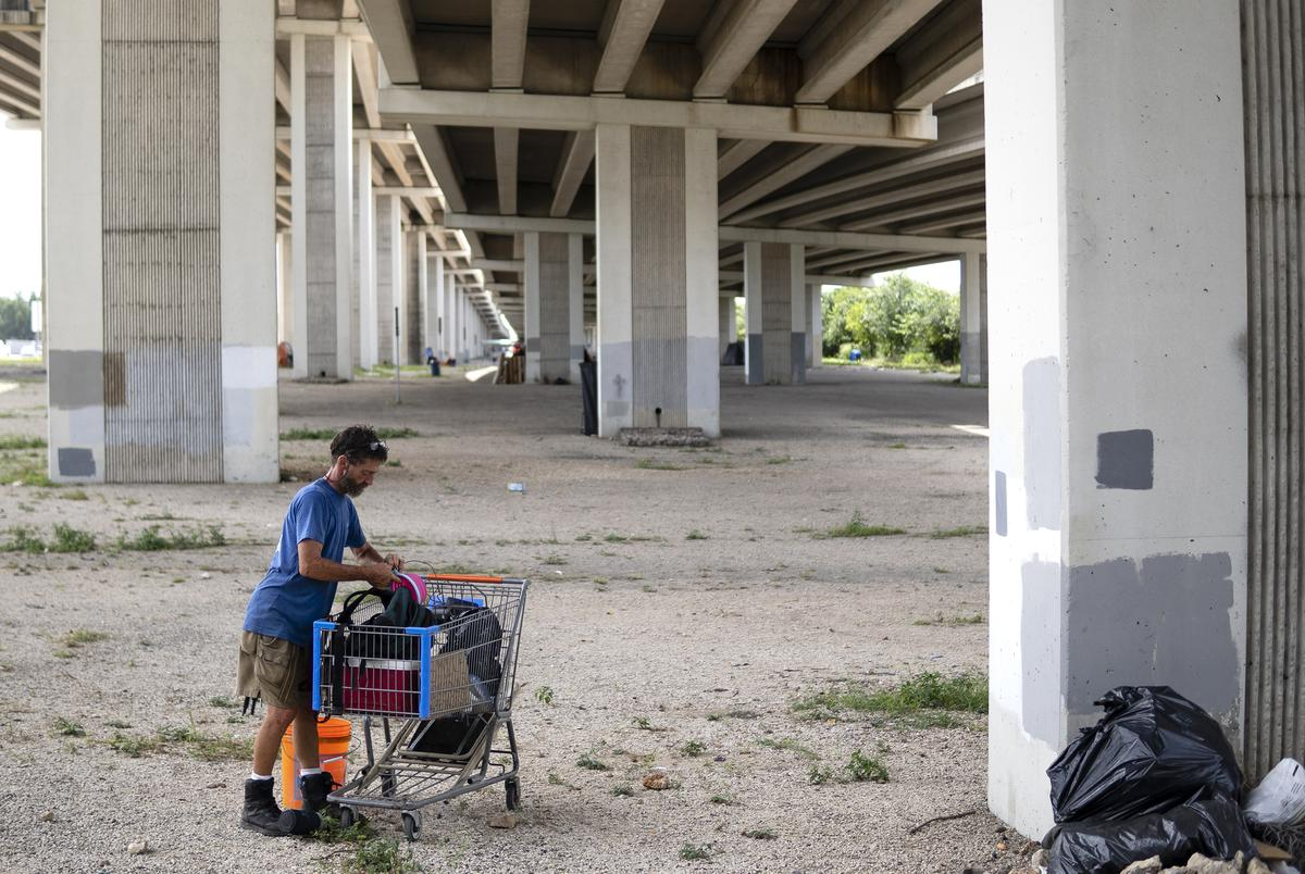 """Anthony Graham, 55, who is known as """"Tigger"""" and has been unhoused for twelve years, packs up belongings from his cart at an encampment underneath Ben White Blvd. on July 27, 2021.Source diversity info: White Male"""