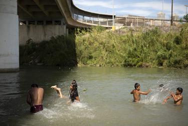 A group of migrants swim in the Rio Grande under the Gateway International Bridge on Oct. 16, 2019.