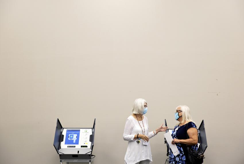 Joan Mooneyham and Barb Walters chat near polling machines set six feet apart at a training lab at the Collin County Electio…