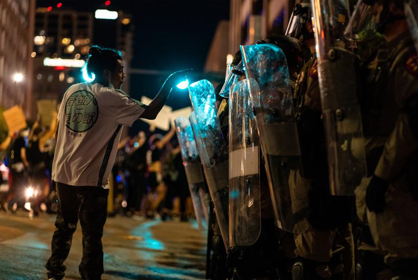 A protester confronts police in riot gear in downtown Austin on August 1, 2020.