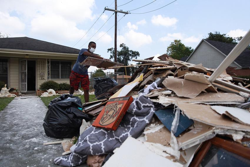 Myles Broussard tosses pieces of drywall into a pile of trash and storm debris outside his home in Beaumont, Texas on Sept...