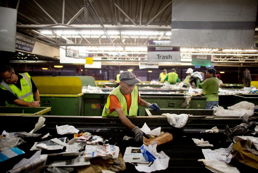A Greenstar Recycling Center employee removes plastic bags from a sort line in Garland, Texas.