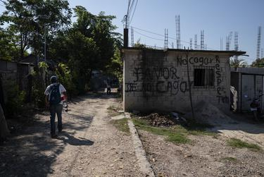 "More than 50 migrants, all Honduran with the exception of one Guatemalan, walk to the nearest train station on Oct. 26, 2018, near Palenque, Chiapas. The graffiti reads, ""Please do not shit here. Be respectful."""