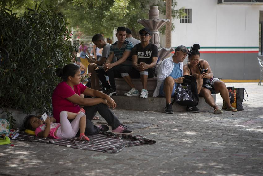 A group of migrants wait at a small plaza near the Gateway International Bridge in Matamoros, Tamualipas. The group is waiti…