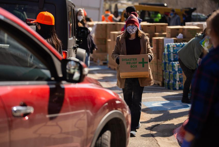 Volunteers distribute boxes of food at a distribution site in Austin on Feb. 19, 2021.