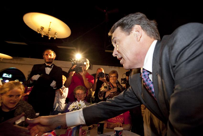 Governor Rick Perry shakes hands with patrons at the Electric Park Ballroom in Waterloo upon his arrival in Iowa on August 1…