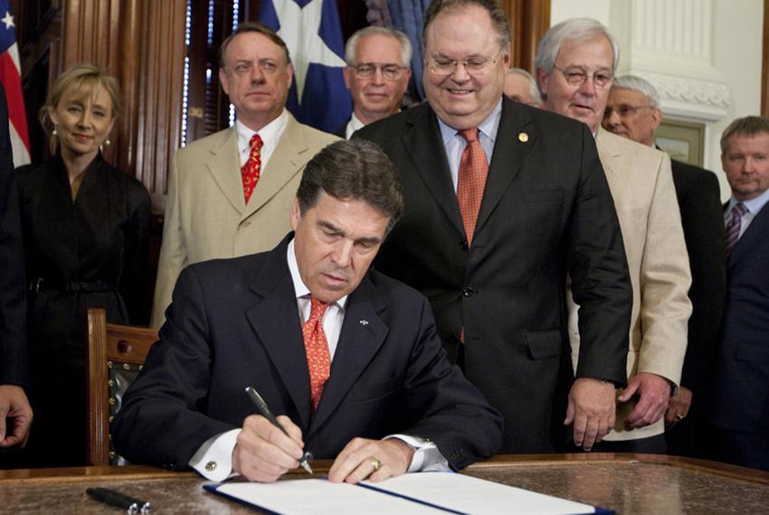 Gov. Rick Perry ceremonially signs Senate Bill 18, a piece of eminent domain legislation, on May 23, 2011, beside state Sen.…
