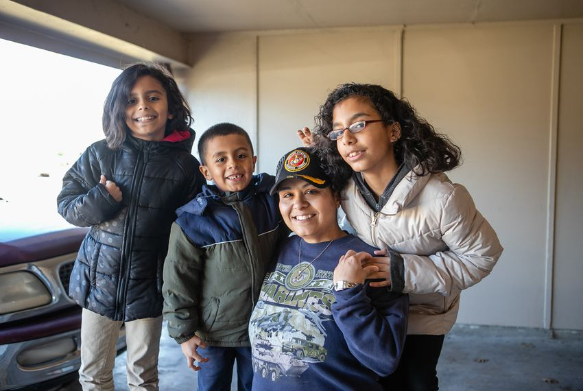 Frances Sanchez and her three children (from left) Samaria or Sammy Sanchez, 9, Pedro Sanchez, 6, and Katrina Sanchez, soon to be 13, pose for a portrait in the home of a friend where they are staying in Garland.