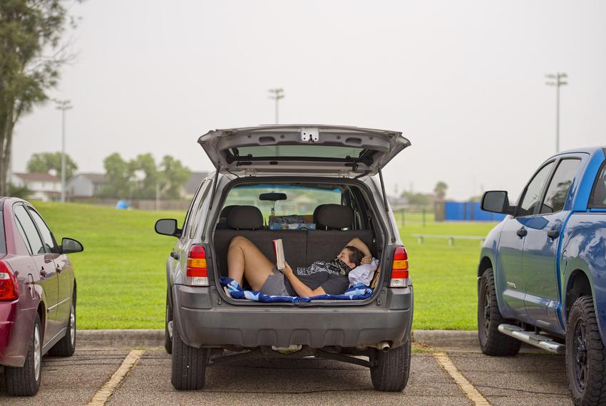 A woman reads in her car while waiting to get tested at the Portland Community Center.