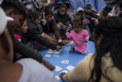 Asylum seeking teenagers learn about factors with poker cards during a class taught by volunteers from the U.S. near the Gateway International Bridge in Matamoros, Mexico on Sunday, Oct. 13, 2019. The kids are not attending school and Sundays are the only days they get to learn from teachers and volunteers. Verónica G. Cárdenas for The Texas Tribune