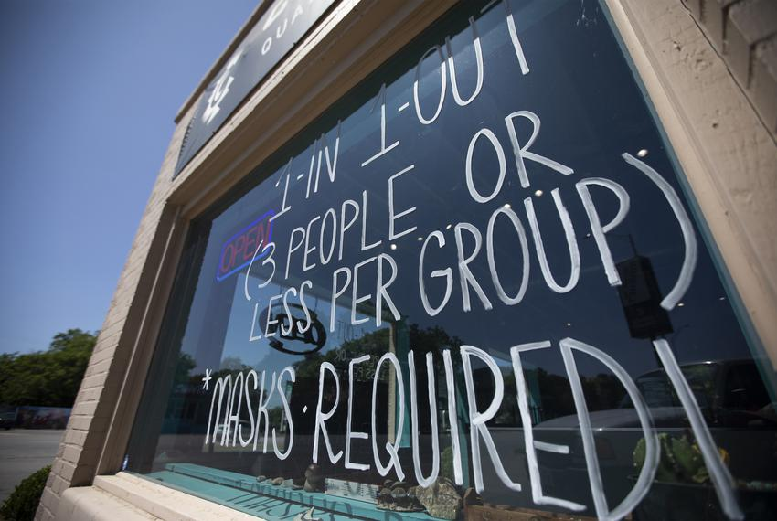 A sign requiring masks is posted at Cosmic Cowboy on South Congress Avenue on Austin. May 8, 2020.