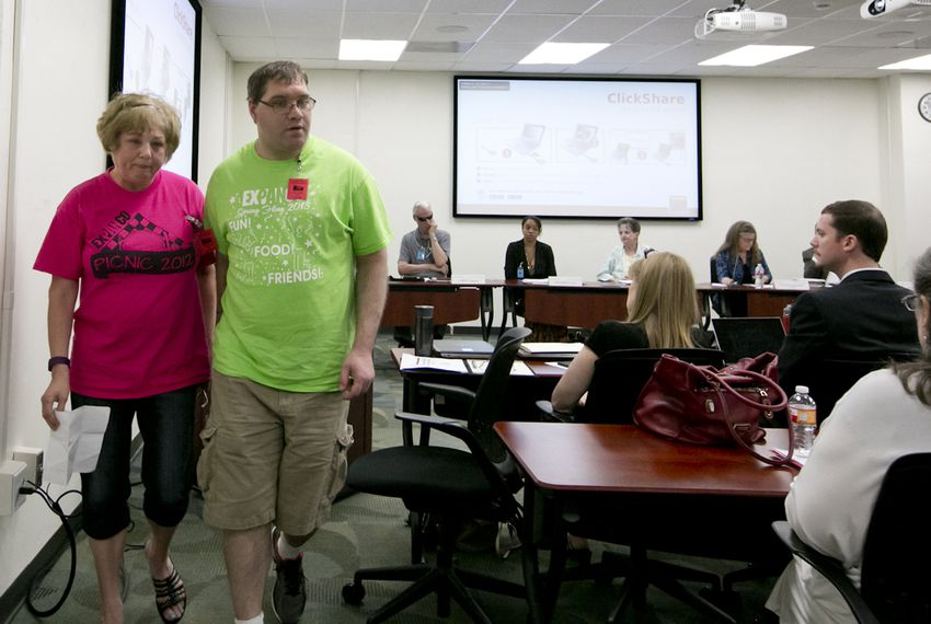 Linda Patrick and her son Scott walk back to their seat after speaking at a May 13, 2016 hearing in favor of a state program that encourages state agencies to contract with companies that hire people with disabilities, including ones that pay some workers less than minimum wage.