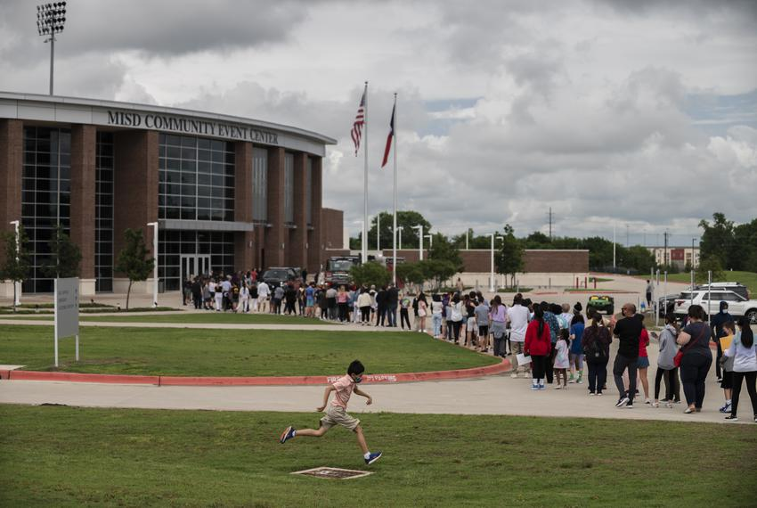 A young boy jumps over a drainage fence as McKinney ISD students and their legal guardians stand in a line to receive a COVI…
