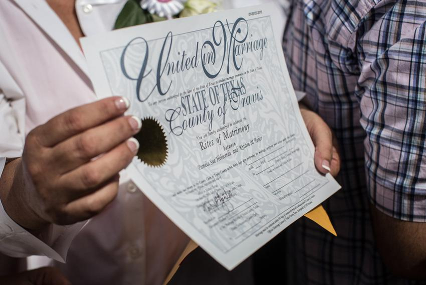 Pamela Holwerds holds up her marriage license following the ceremony that married over 40 same-sex couples on the south lawn…