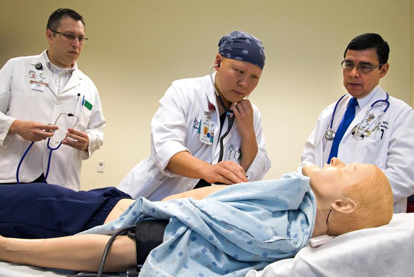 Third-year medical student Summer Scavone (middle) tries to listen to the SimMan's lungs for wheezing.