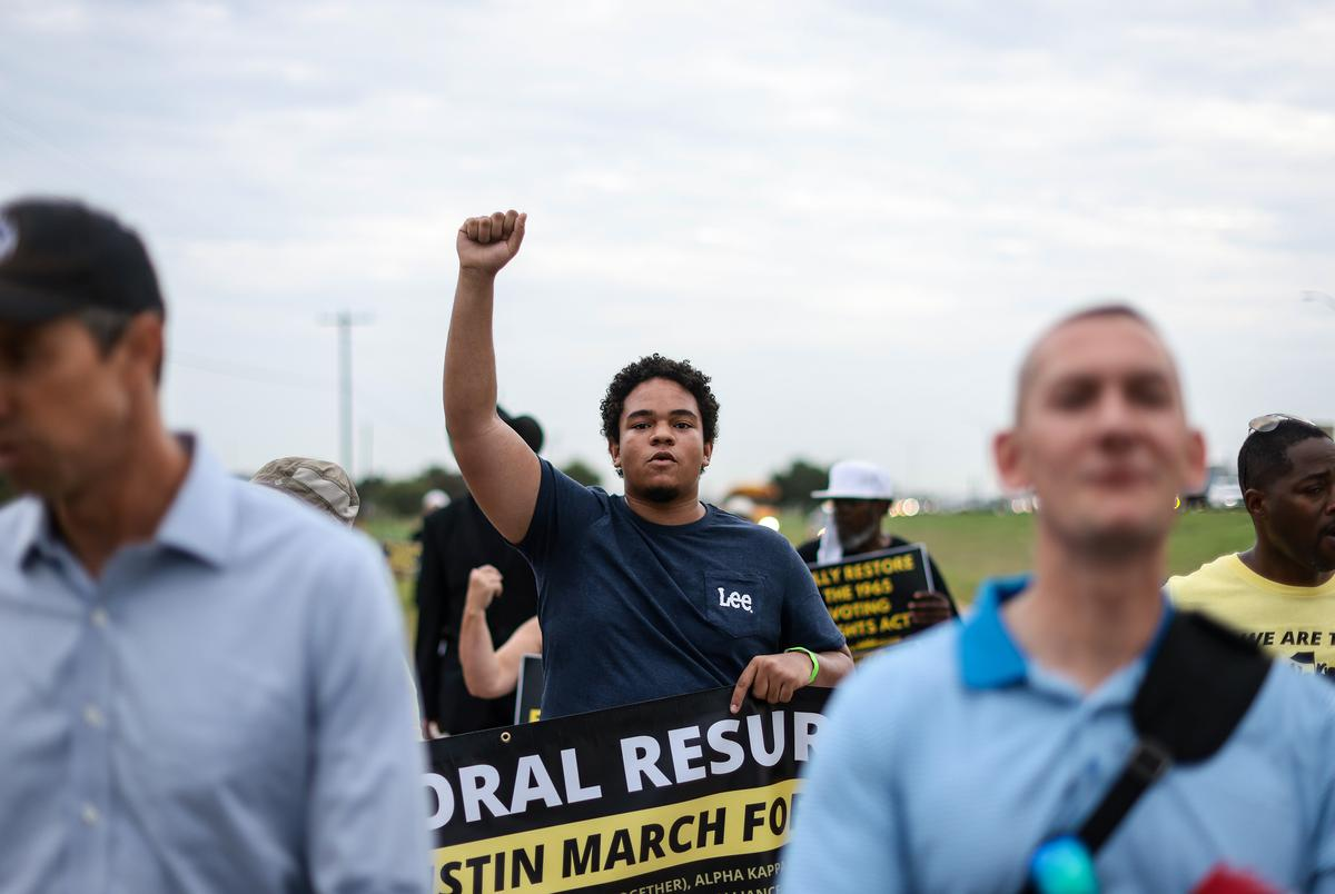 Marcel McClinton marched with his fist raised along the access road of Interstate 35 in Georgetown on July 28, 2021.