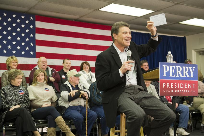 Rick Perry grins as he holds up a paper that symbolizes his flat tax plan during a stop in Osceola, Iowa on December 27, 201…