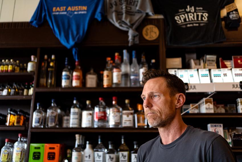 Billy Benedict, the owner of J&J Spirits in Austin's historic East 11th street, poses for a photo amid the economic uncert...