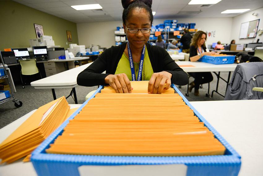 Ballot-by-mail clerk Chaundra Grattan organizes ballot packages at the Travis County Elections Division in Austin on May 19,…