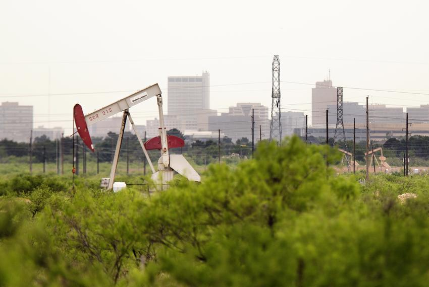 Midland's skyline is a backdrop for another pump jack that has ceased to move its head as oil prices continue to drop.