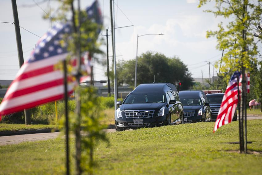 A hearse containing the body of George Floyd drives up a flag-lined street as it approaches the Fountain of Praise Church in…