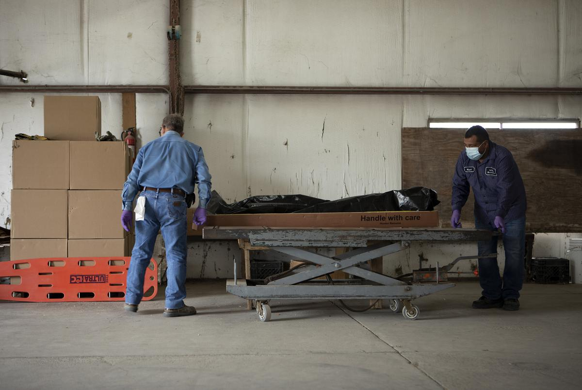 From left, Al Luna and Miguel Guzman move the body of someone that recently died from COVID-19 onto a table. They will shortly place the body inside an incinerator at the crematorium at Val Verde Memorial Gardens. July 17, 2020.