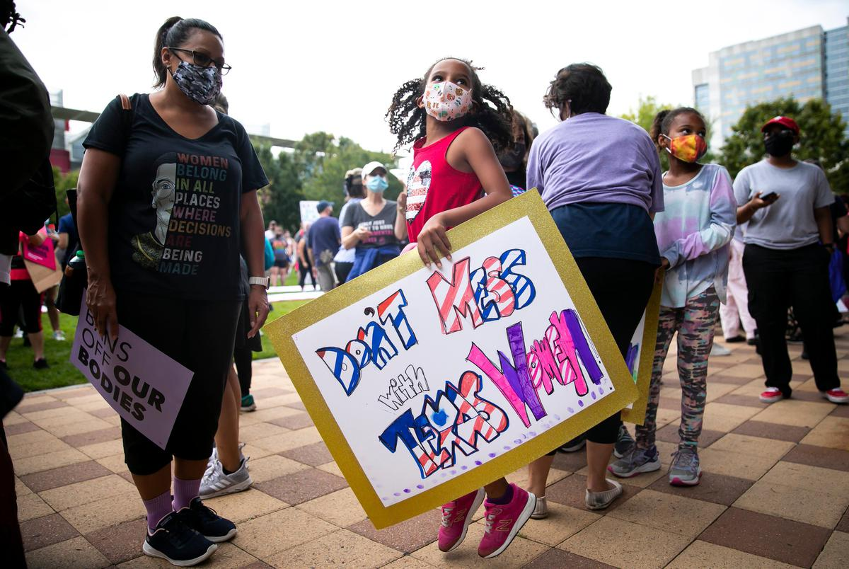 A young participant jumps a with a sign as people gather for the 2021 Women's March on Texas at Discovery Green in downtown Houston on Oct. 2, 2021.