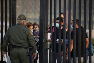 A group of migrants wait to turn themselves over to National Guard and Customs and Border Patrol officials at the U.S. and Mexico border in Del Rio on July 22, 2021.