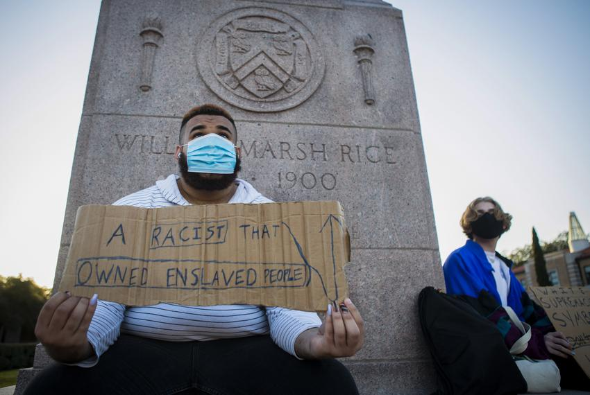 Shifa Rahman, left, holds a protest sign at the base of the William Marsh Rice statue on the campus of Rice University  on J…