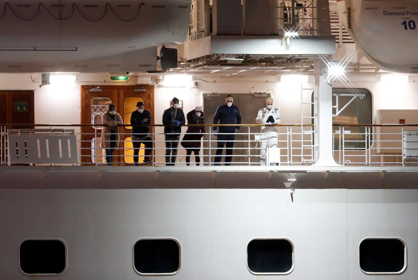 Passengers on deck wave to other passengers as they leave the coronavirus-hit cruise ship Diamond Princess at the Daikoku ...