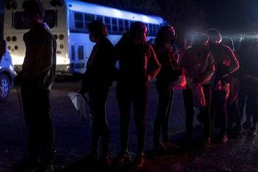 A group of unaccompanied minors wait to be transported by U.S. Customs and Border Patrol after crossing the Rio Grande into the United States from Mexico in Roma on April 7, 2021.