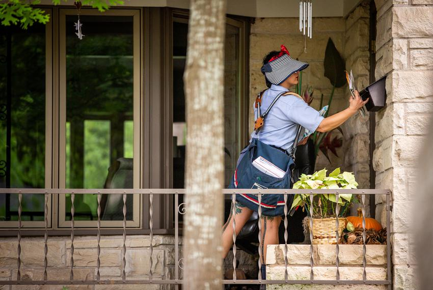 USPS employee Sweetie Dionne delivers mail on her usual route in the Cherrywood neighborhood in Austin on April 6, 2020.