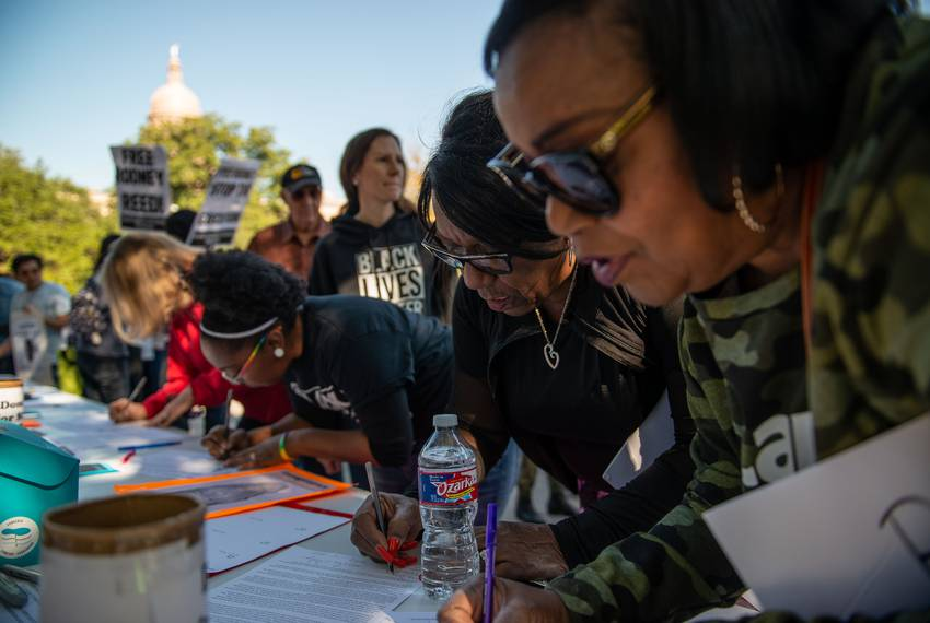 Rodney Reed's cousins Delores Ferguson, center, and Patricia Reed, right sign a clemency letter before a rally in front of...